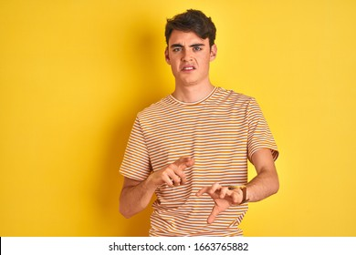 Teenager boy wearing yellow t-shirt over isolated background disgusted expression, displeased and fearful doing disgust face because aversion reaction. With hands raised. Annoying concept.