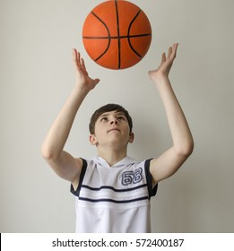 Teenager boy in a white shirt with a ball for basketball on a light background
