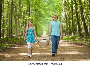 Teenager brother and sister walking along the path in the woods, carrying picnic basket
