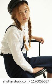 A teenager in a cap sits on a chair. Portrait. Fashion clothes.
