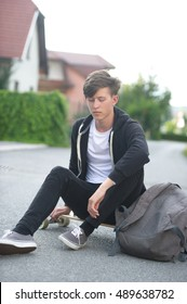 Teenager casually sitting on his board while looking downwards.