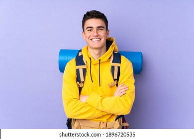 Teenager caucasian mountaineer man with a big backpack isolated on purple background laughing