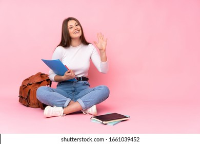 Teenager caucasian student girl sitting on the floor isolated on pink background saluting with hand with happy expression