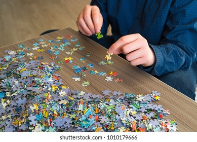 Teenager collects puzzles on coffee table.