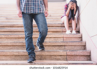 Teenager couple breaking up and ending relation after argument. Boyfriend legs leaves his sad girlfriend and go away. Filtered image.