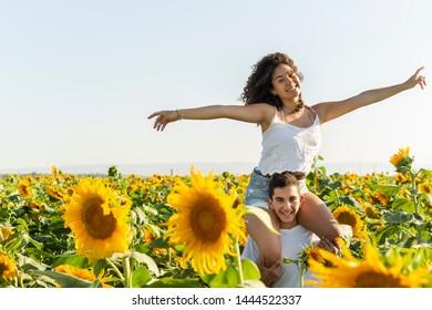 Teenager couple/siblings having fun in a sunflowers field.