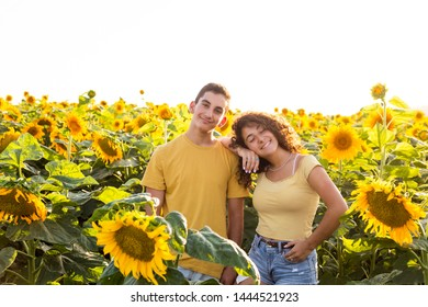 Teenager couple/siblings in a sunflowers field.