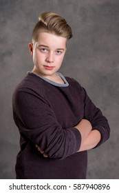 teenager with crossed arms in front of gray background