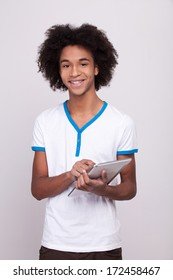 Teenager with digital tablet. Cheerful African teenager working on digital tablet and smiling while standing isolated on grey background