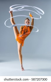 teenager doing gymnastics dance with white ribbon on a blue background. The girl in the orange dancing suit