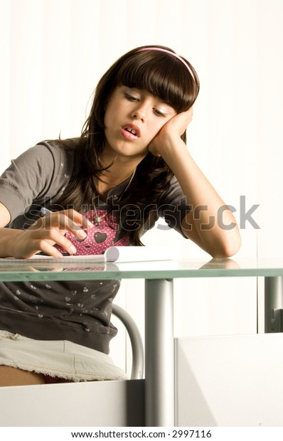 Teenager doing homework at desk looking confused