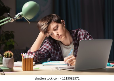 Teenager doing homework at table in evening