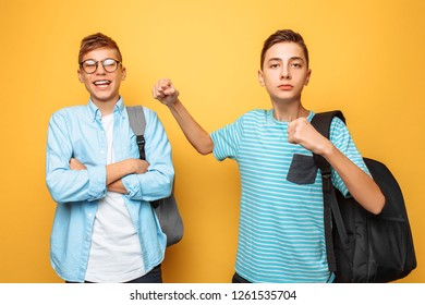 Teenager dominates brother, fist, on yellow background