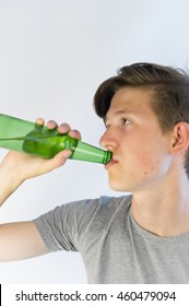 Teenager drinking beer from a bottle.