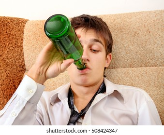 Teenager drinks a Beer on the Sofa at the Home