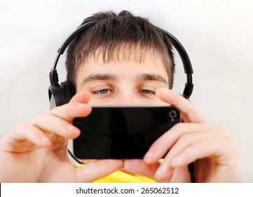 Teenager in Earphones with Cellphone on the White Wall Background closeup