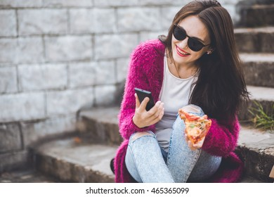 Teenager eating pizza in street and browsing internet on phone