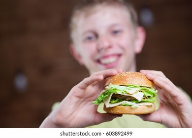 A teenager eating a sandwich with cheese and chop
