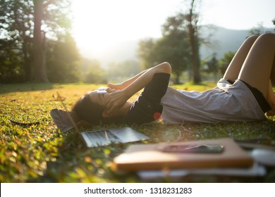 teenager female happy moment and listen music from smartphone on the green grass field