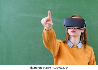 Teenager female student wearing virtual reality glasses in classroom at school. Innovative teaching methods. Education concept.