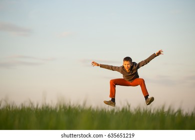 The teenager is flying over the field at sunset