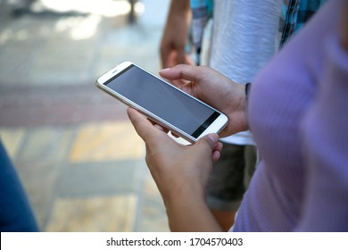teenager friend group standing outdoor using their smart phone having fun together ,social media and technology internet with people concept background