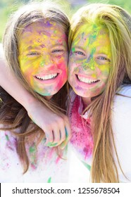Teenager friends with dry colors. Colorful holi on painted face Drycolors. Teenage school friends having fun piggybacking outdoors with dry colors. Happy mood with colorful drycolors