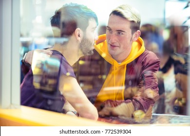 Teenager Gay couple chatting in a restaurant .Candid shot behind window with reflections