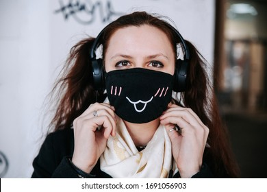 Teenager girl in anti-bacterial cartoon face mask with funny teeth pattern in city street