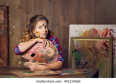 Teenager girl is in the art studio sitting at the table leaning on the palette