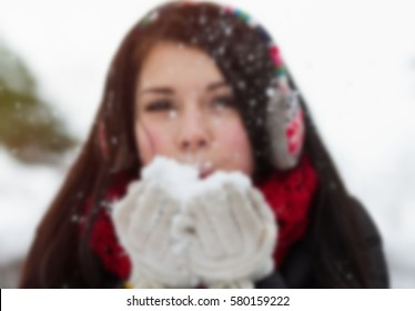 Teenager girl blowing fluffy snow form her hands in winter.Blurry background.Funny young girl have fun outdoor in cold snowy winter day.Cute female model.Winter back ground.Out of focus blur
