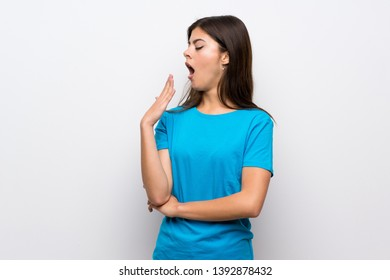 Teenager girl with blue shirt yawning and covering wide open mouth with hand