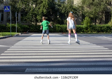 Teenager girl with brother rolling skating at a pedestrian crossing