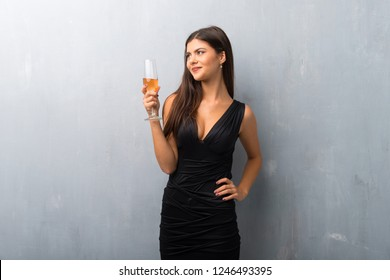 Teenager girl with champagne celebrating new year 2019 posing with arms at hip