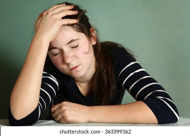 teenager girl close up portrait with severe headache grimace of pain on blue wall background