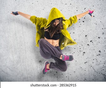 Teenager girl dancing hip hop over textured background