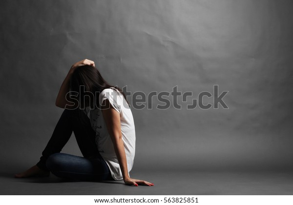 Teenager girl with depression sitting alone on the floor in the dark room