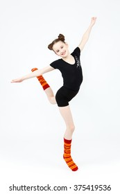 Teenager girl doing gymnastics dance in jumping on a white background