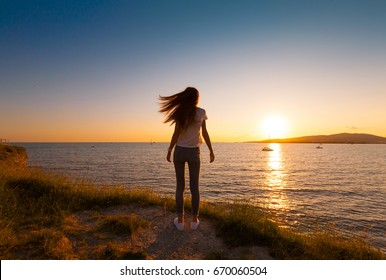 A teenager girl enjoying view sea. She has slim body, long hair. Journey in holidays. Beautiful summer sunset landscape. Happy vacation. Summer rest in coast. People portrait.