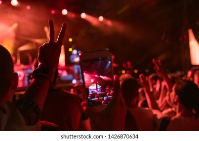 Teenager girl fan raised hand with V sign Gesture and shooting vertical video with smartphone popular band on the night concert. Colorful crowdy background entertainment with light and laser show.