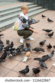 Teenager girl feeds the pigeons in a square