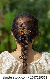 Teenager girl head back view with plait and hair clips on the summer green background. Decoration Hair Clip on beautiful hair style.
