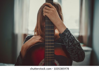 teenager girl hiding behind guitar. With window backlight