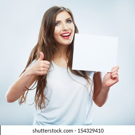Teenager girl hold white blank paper. Thumb up.Young smiling woman show blank card. Girl portrait