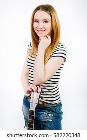 Teenager girl holding acoustic guitar isolated on the white background