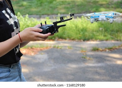 Teenager girl holding drone control panet and flying blue copter on blurred green background