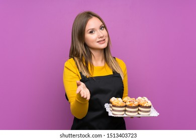 Teenager girl holding lots of different mini cakes over isolated purple background handshaking after good deal