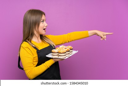 Teenager girl holding lots of different mini cakes over isolated purple background pointing finger to the side