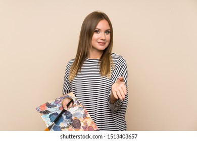 Teenager girl holding a palette over isolated background handshaking after good deal
