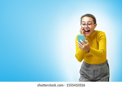 A teenager girl holds a mobile phone in her hands and speaks via video call and laughs. The background is light blue.